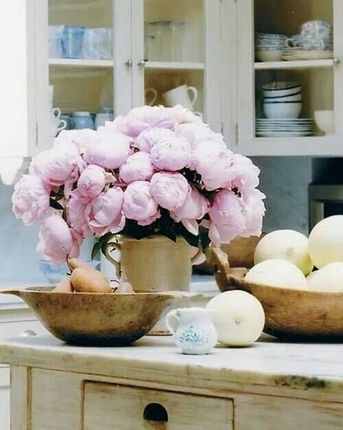 Pink peonies and antique wooden bowls in this farmhouse cottage kitchen