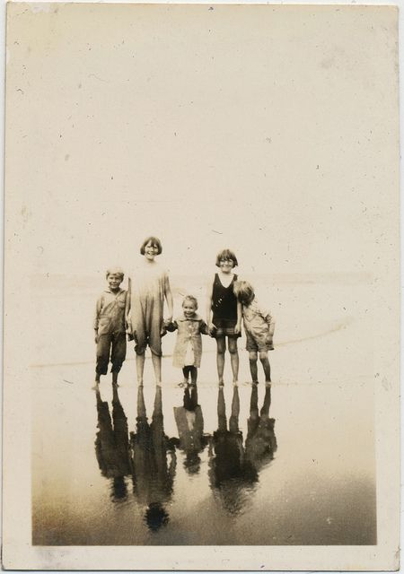 Five children standing together on the seashore. Their reflections can clearly be seen before them in the calm watery sand.