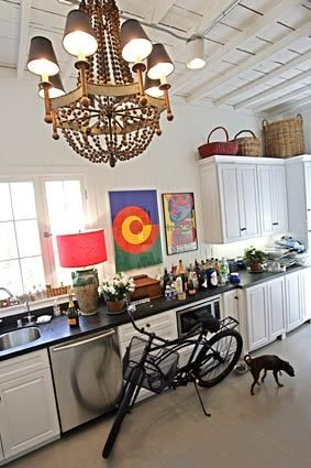 An ornate light fixture and Hartig's black Schwinn bike add whimsy to his kitchen with its white walls and cabinets, dark granite counters a...