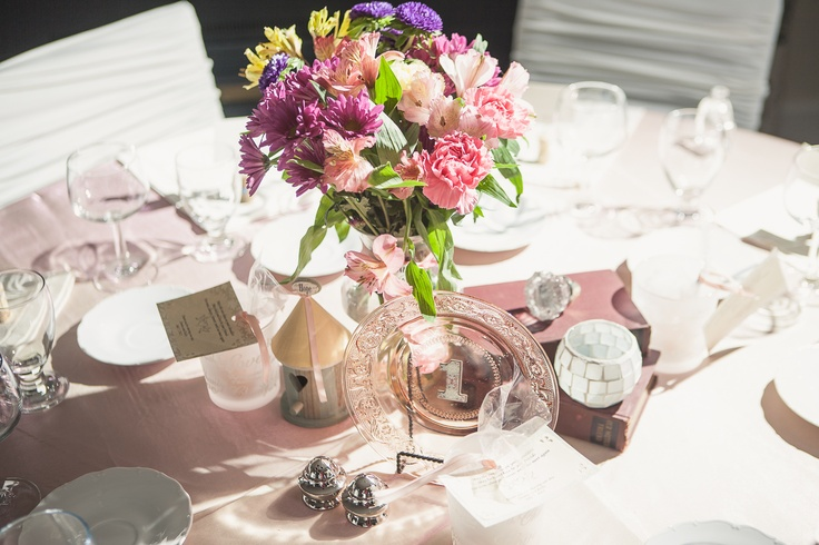 Vintage table centrepieces, books, birdhouses, glass door knobs, candle and mixed flowers