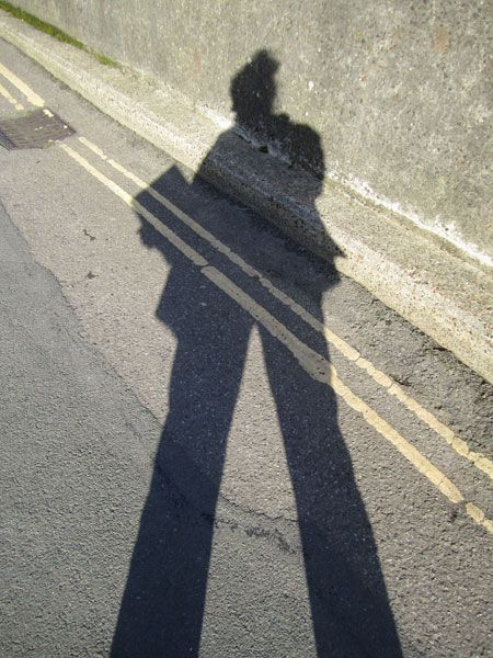 My shadow holding our new book (against the sea wall)