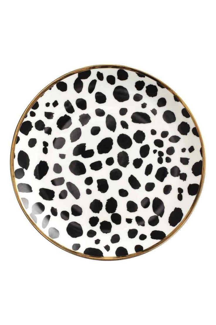 Plato con motivo de leopardo: Plato de porcelana con motivo de leopardo y borde dorado. Diámetro 21 cm.