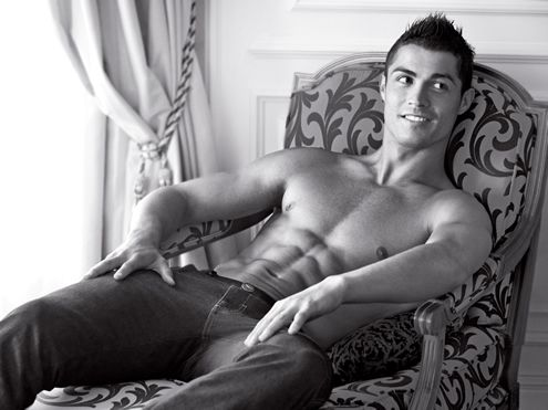 Cristiano Ronaldo in Armani photoshoot, sitting on a chair, showing his well defined six-pack abs
