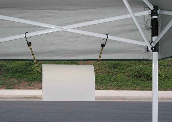Hang a paper towel roll using a bungee cord from the tent struts