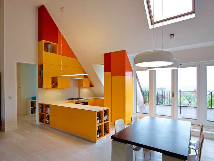 Orange Iceberg Apartment - A joyfully coloured kitchen animates the open-plan living area and becomes the focus of the family activities. A sculptural geometry contains all storage while robust operational areas are strategically placed to allow panoramic views of London. The tall cabinets are tailored to the form and scale of the generous pitched roof and all appliances are seamlessly integrated.