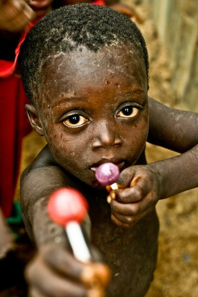 Beautiful photo of a young African boy with a lollipop. He has such striking big brown eyes.