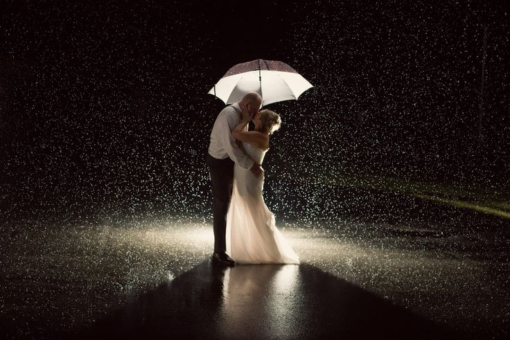 Three Leaf Photography | Abbotsford Chilliwack Langley Wedding Photographers - Bride and groom under an umbrella in the rain. Backlit showing raindrops