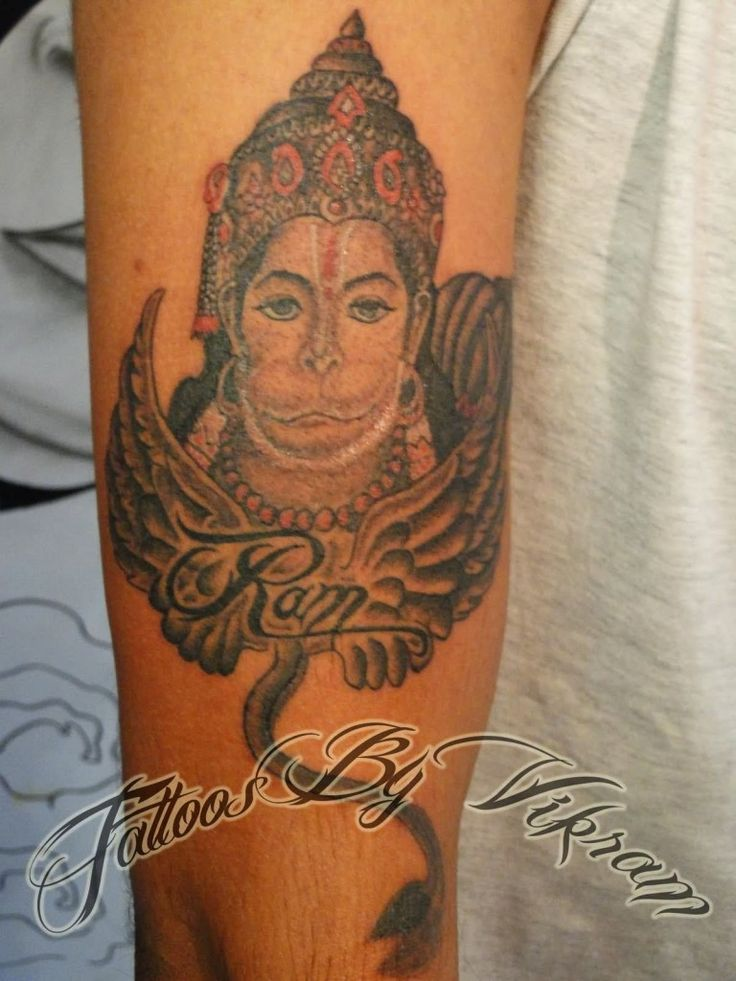 wings and hanuman tattoo on arm