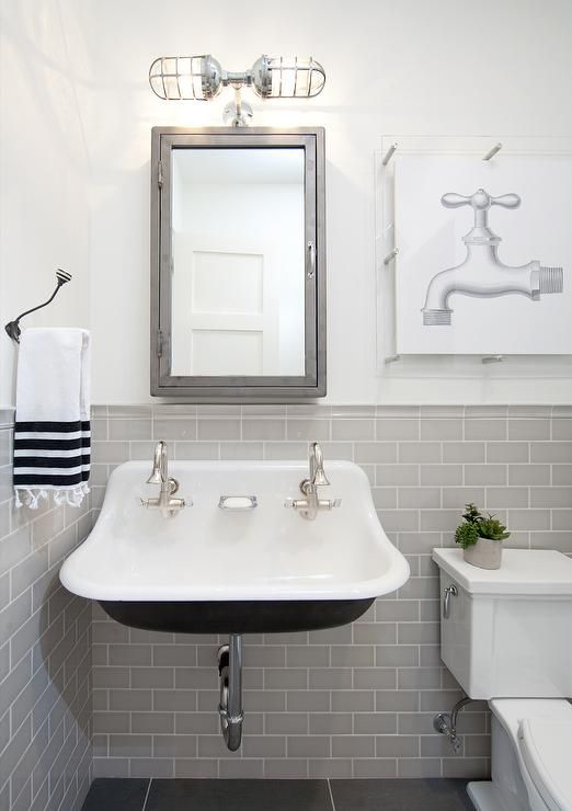 Charming gray and black industrial kids bathroom features white walls lined with gray subway tiles accented with white grout covering the lower walls highlighting black slate floor tiles.