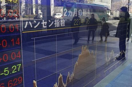 People are reflected on the electronic board of a securities firm in Tokyo, Monday, Jan. 16 2017. Asian shares were mostly lower Monday morning amid worries about Britain's exit from the European Union, and Takata stock dropped in Tokyo after the air bag maker agreed to a guilty plea in the U.S. over massive recalls. (AP Photo/Koji Sasahara)