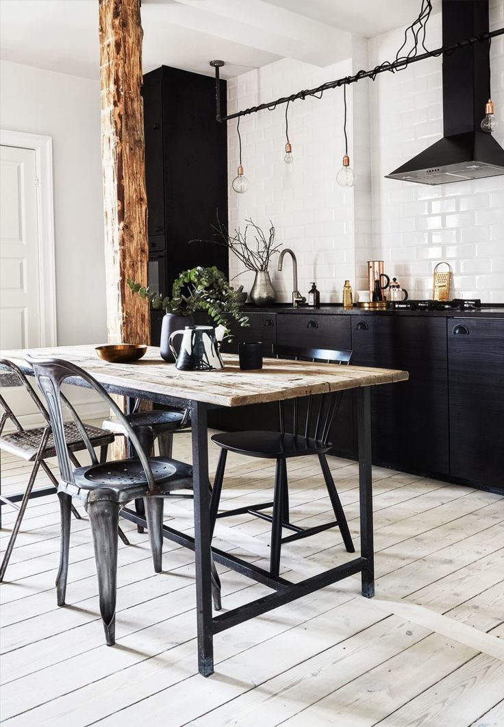 Rustic dining kitchen space with hardwood flooring, subway tiles and industrial dining furniture that signals a cool New Yorker look.