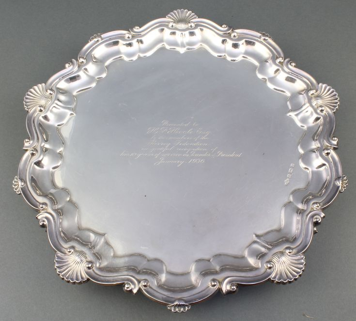 Lot 582, A silver salver with fancy scroll and shell rim and presentation inscription Birmingham 1933, 910 grams Est £250-300