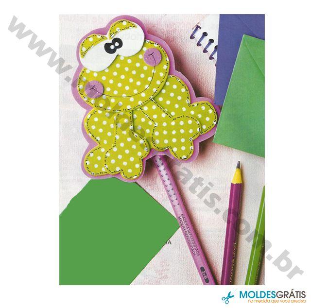 Ponteira-de-Lápis Sapinho  Retalhos de EVA com 3mm de espessura nas cores: branco, rosa, verde com poá e rosa com glíter. Base  de EVA rosa para ponteira do lápis. Cola instantânea. Caneta permanente preta. Tesoura. Tinta relevo branca. Lápis. Molde.