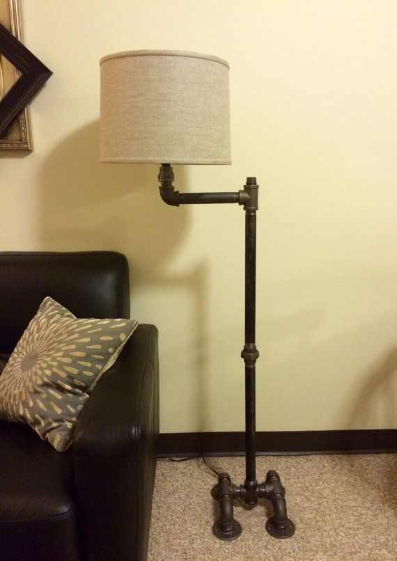 Floor lamp constructed from black malleable iron plumbing pipe. This lamp is sure to light up any room with a blend of industrial edge and
