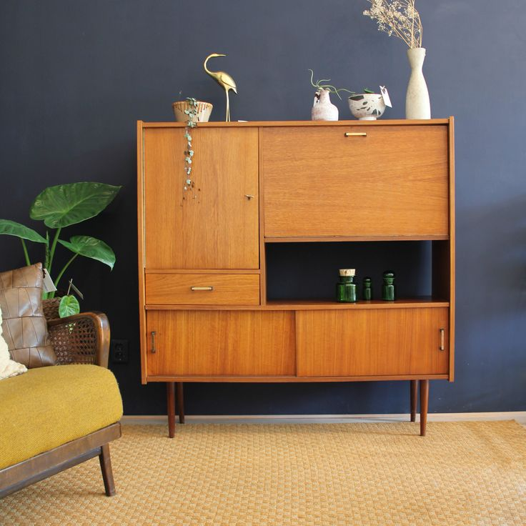 Sixties highboard on a blue wall with brass bird, vases, yellow vintage chair, plant alocasia