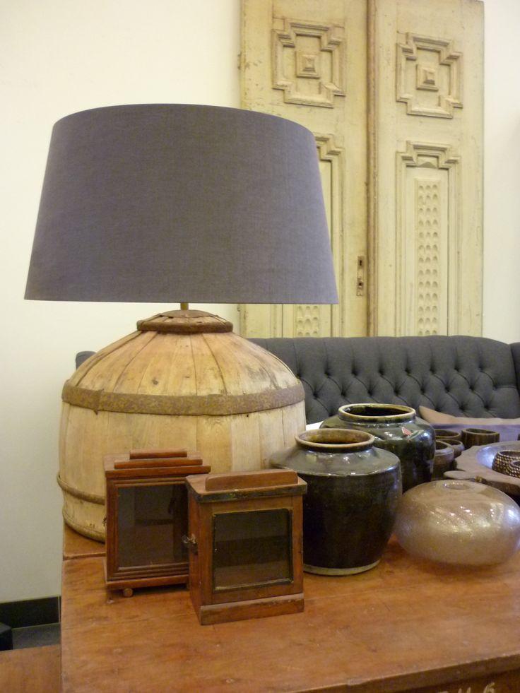 Interieur in bruin en antraciet; lampvoet gemaakt van oude ton, oude Indiase klokkastjes, oude deuren, gecapitonneerde bank.