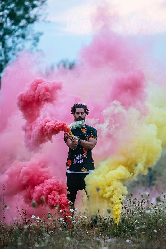 fashionable hipster man holding colorful smoke bombs in  nature
