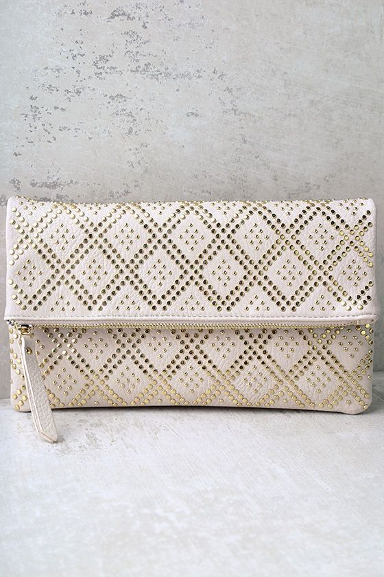 "The Crowd Pleaser Cream Studded Clutch has a little something for everyone! Vegan leather, embellished with a gold, studded pattern, constructs this fold-over clutch with a hidden magnet closure that reveals a flap pocket (plus zipper pocket and wall pocket). Unzip top to access an interior compartment with space for all your goodies! Carry as a clutch, or attach the 48"" gold chain strap (with shoulder pad)."