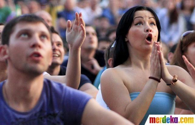 Sejumlah penonton sepak bola bersorak saat menyaksikan pertandingan Spanyol melawan Italia lewat layar besar di Kiev, Ukraina.