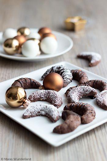 Weihnachtsbäckerei, die 3te: Brownie-Kipferl  ZUTATEN (für ca 35 Stück)      50g Zartbitterschokolade     130 – 170g Mehl (der Teig sollte nicht zu bröselig werden)     1 EL Kakao     30g Haselnüsse, gemahlen     30g Mandeln, gemahlen     30g Zucker     1 Päckchen Vanillezucker     1 Prise Salz     1 Eigelb (Größe M)     120g kalte Butter     Puderzucker und Zartbitterkuvertüre zur Dekoration…