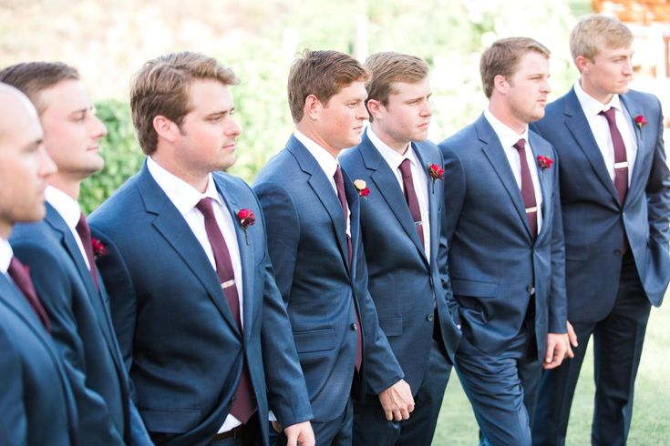 Classic groomsmen look.  Navy suits, maroon ties, tie clips.  Red and orange wedding flowers.  Wedding Photography by www.leahvis.com.
