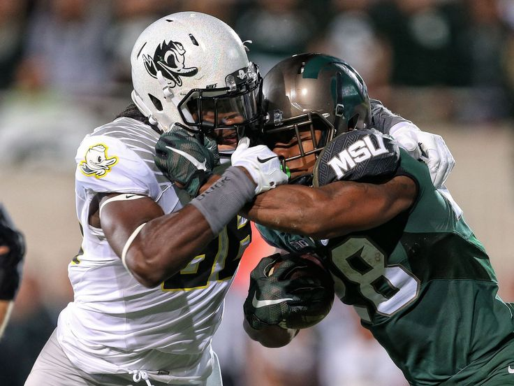 Michigan State Spartans running back LJ Scott (3) is tackled by Oregon Ducks defensive lineman Tui Talia (55) during the 1st half of a game at Spartan Stadium.  Mike Carter, USA TODAY Sports