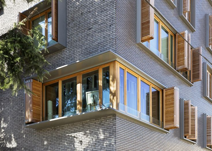 Michel Guthmann pairs grey brick with larch for Paris housing block. Dynamic exterior shading.