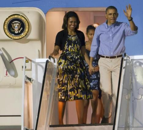 December 23, 2013 President Barack Obama & First Lady Michelle arrived at Joint Base Pearl Harbor-Hickam in Honolulu, Hawaii. The Obama family spent their annual holiday vacation in Hawaii, returning to Washington on January 5.     Landing in Honolulu, Mrs. O wore a vibrant printed sundress paired with a cropped black cardigan. Gold hoops completed the warm weather look.    Mrs. Obama is  wearing a Modern Camo dress by Tracy Reese.  via Mrs-O.com