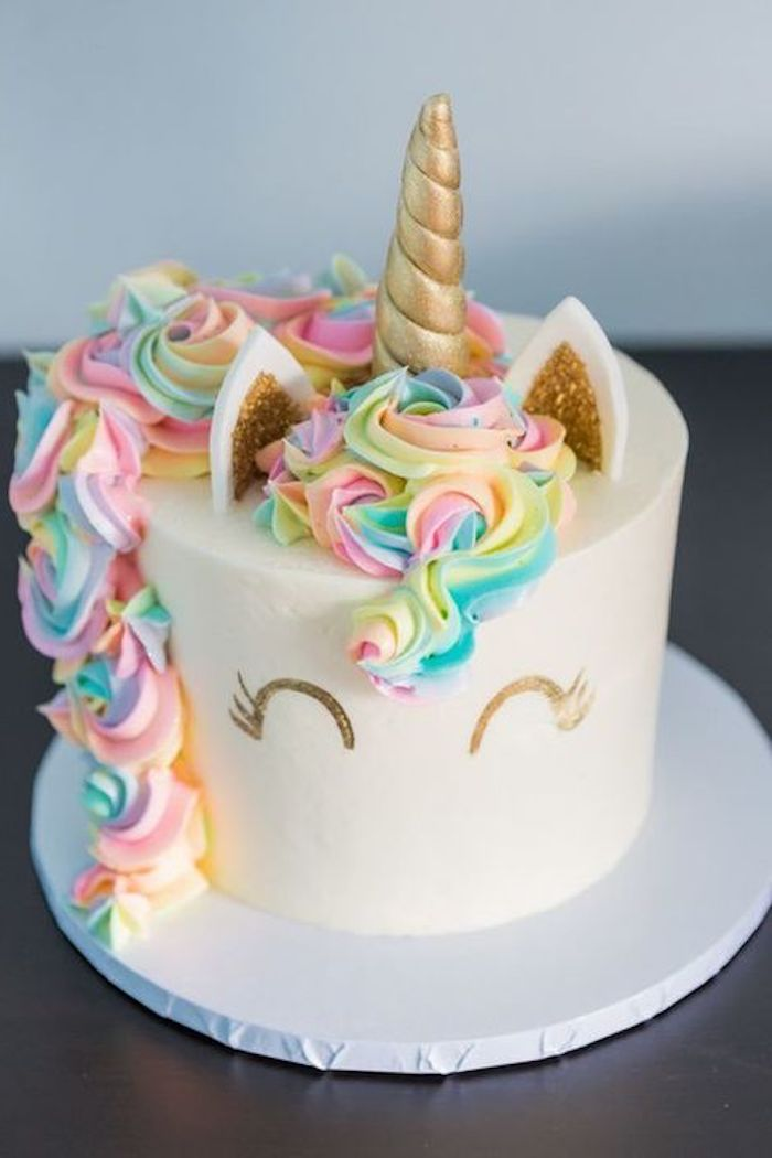 hier ist eine weisse einhorn torte mit einem weissen einhorn mit einer bunten mahne aus sahne und mut kleinen ohren und einem goldenen horn idee fur einhorn