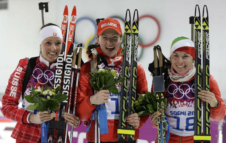Silver medalist Switzerland's Selina Gasparin, left, gold medalist Belarus' Darya Domracheva, center, and bronze medalist Belarus' Nadezhda Skardino pose after the women's biathlon 15k individual race, at the 2014 Winter Olympics, Friday, Feb. 14, 2014, in Krasnaya Polyana, Russia. (AP Photo/Lee Jin-man)