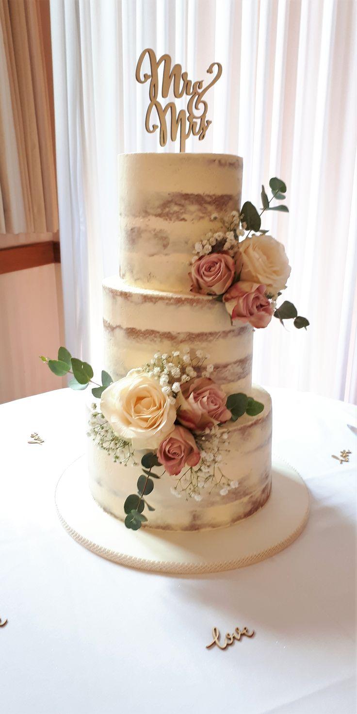 Schöne dreistufige nackte Hochzeitstorte – dekoriert mit Blumen und Gypsophila. …   – Wedding cake