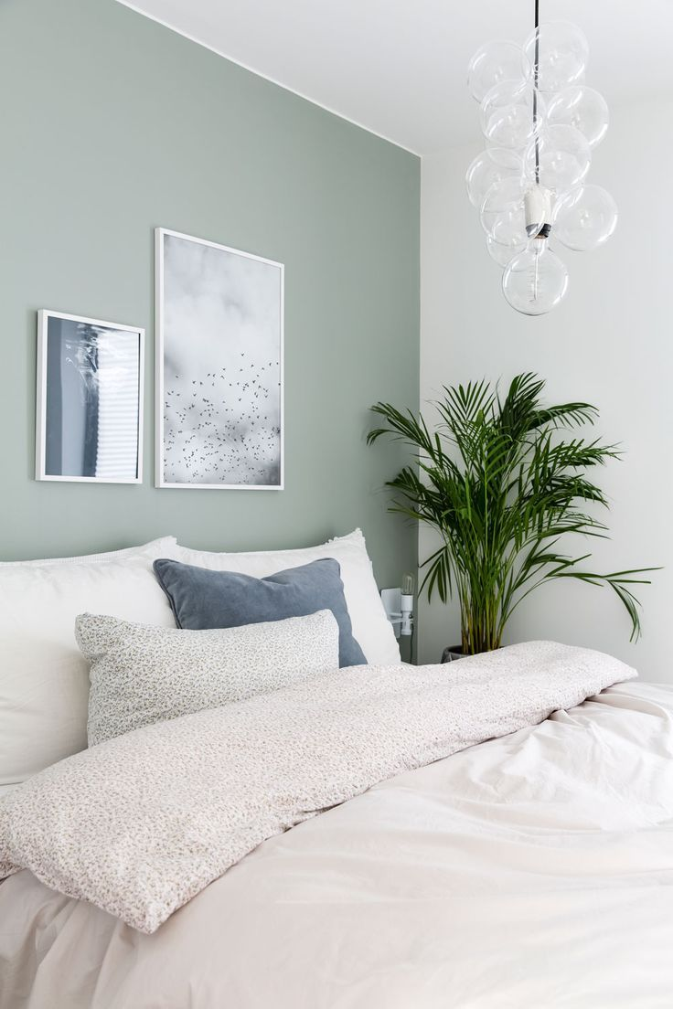 Neutral minimal bedroom decor with white bedding and pale green walls