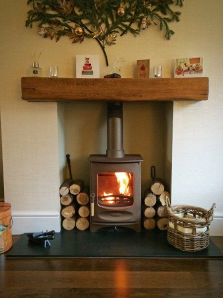 Charnwood C-Four in bronze, honed granite hearth, medium character medium colour oak fireplace beam. Christmas decorations.