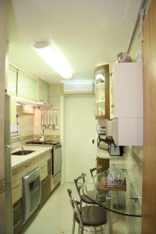 Até a área de refeições aparece nesta cozinha projetada por Patrícia Moraes: uma bancada curva de vidro ocupa uma das paredes. O design sinuoso também aparece nos armários.