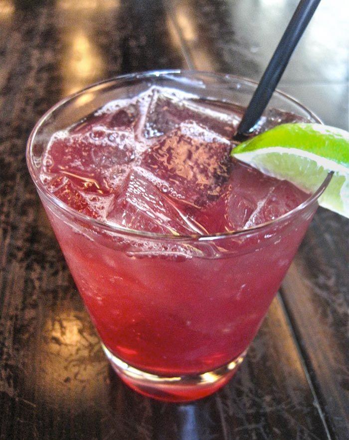 The Grand Veev Cocktail -    2 ounces VeeV, Açai spirit  1 ounce Grand Marnier  1/2 ounce fresh lime juice  1 ounce acai juice  Lime wedge for garnish