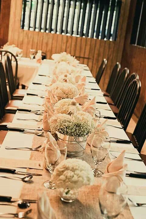 Vintage wedding table with burlap runner and baby breath flowers on cans.