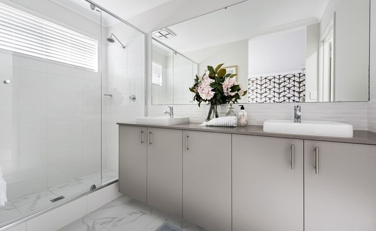 The ensuite features semi-inset vanity basins, mixer taps and glass semi-frameless pivot screen door