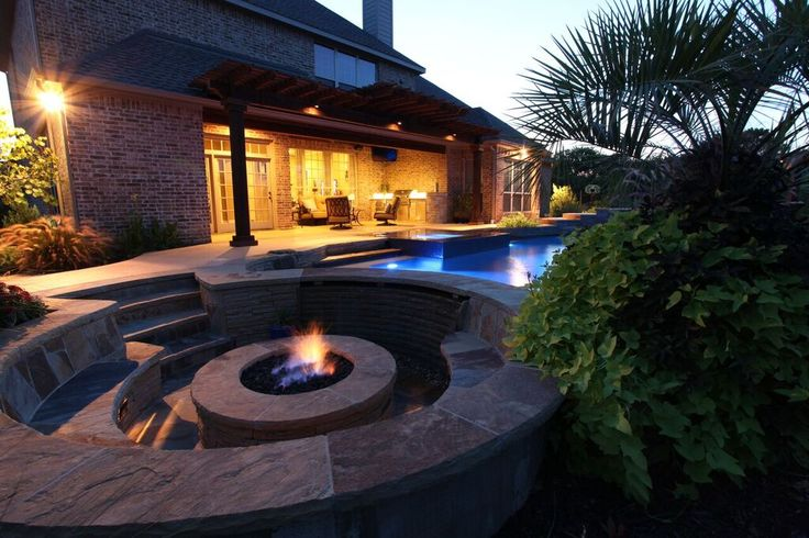 Freeform pool with firepit, natural stone elements by Outdoor Signature in Argyle, Texas