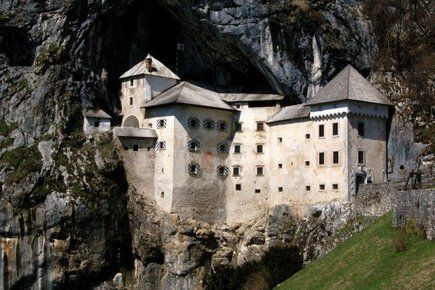 Predjamski Castle in Slovenia is built into the entrance of a cave system that runs through the mountain, making it a seige-proof fortress. It was first constructed in the 13th century, and expanded several times. Predjamski Castle has its own railway and concert hall! You can see panoramic photos of the castle interior, the cave under the castle, and more pictures here.