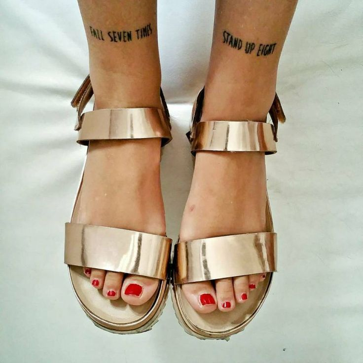 "Tatuajes coincidentes que dicen ""Fall seven times, stand up eight"" (""Cáete siete veces, levántate ocho""), en las espinillas de Chiara Monteleone."