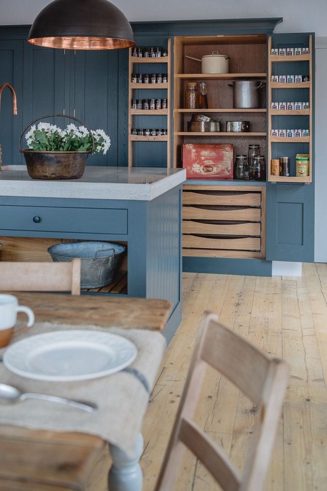 Sustainable Kitchens Showroom. Industrial Shaker style showroom kitchen with oak cabinets painted in Farrow & Ball Down Pipe. The island has a polished concrete worktop with open shelving and slatted wood. The hanging pendant light from Original BTC and bespoke copper tap add to the industrial feel. The open larder with LED lights has built in spice drawers on the doors. The floor is made from reclaimed scaffold planks.