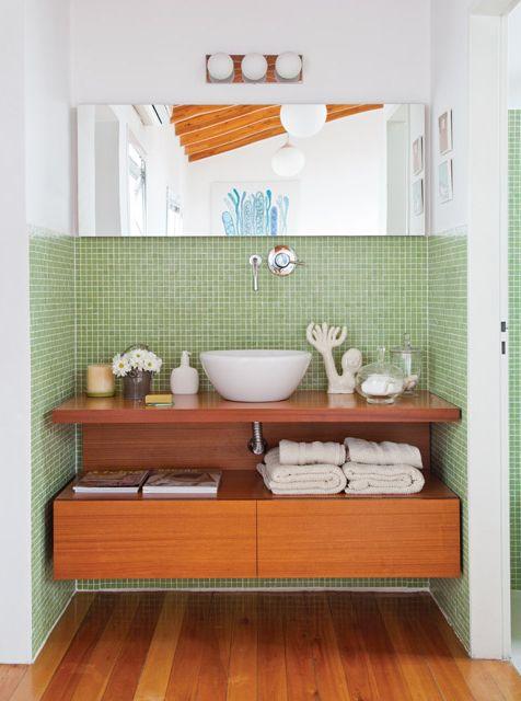 Tocador separado del baño con venecitas verdes, mesa de madera, y mucha luz. Foto: Magalí Saberian
