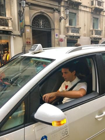 Mika driving a taxi