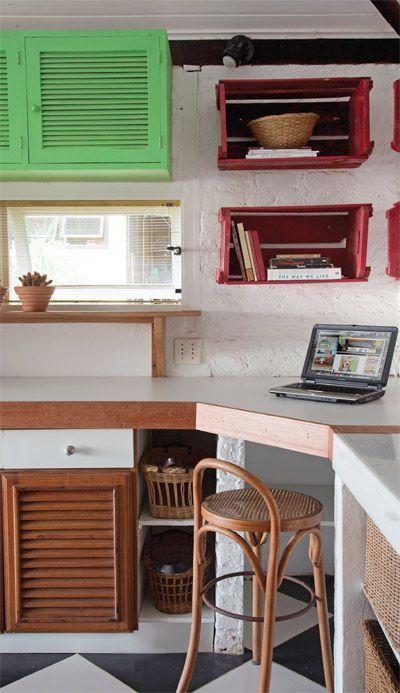 """No cantinho do computador, a estante foi montada com caixotes pintados de vermelho. """"Improvisos como este reforçam o tom descontraído da decoração, quase de uma casa de pescador"""", diz Monica."""
