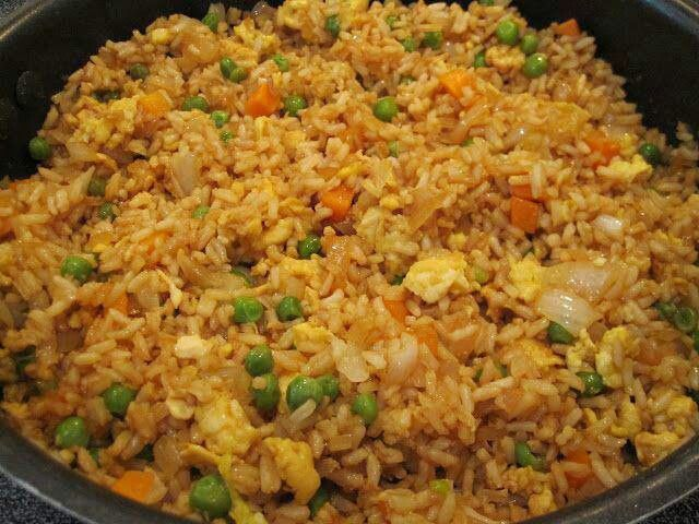 FRIED RICE 3 cups cooked white rice 3 tbs sesame oil 1 cup frozen peas and carrots (thawed) 1 small onion, chopped 1tsp minced garlic 2 eggs, slightly beaten 1/4 cup soy sauce On medium high heat, heat the oil in a large skillet or wok. Add the peas carrots mix, onion and garlic. Stir fry until tender. Lower the heat to medium low and push the