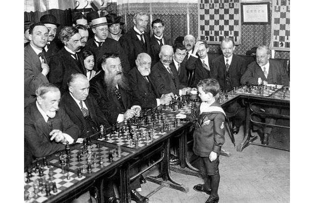 Chess prodigy Samuel Reshevsky was born in Poland, but in 1920, at age eight, his parents moved to the United States so that they could demonstrate his talents. At the time, he was the youngest to ever play in an official chess tournament. Here he is at a simultaneous chess exhibition.