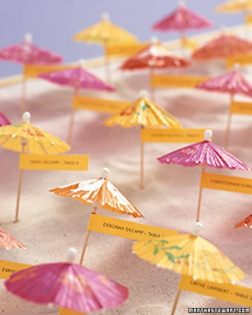 Add a little tropical touch to your event with paper umbrellas to show guests to the proper seat.