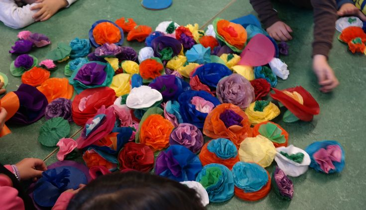 To decorate our classroom everyone pitched in and made flowers from circles of colored tissue paper. We stapled together 5-6 different colors that each child chose and then crunched them up one layer at a time starting from the center.