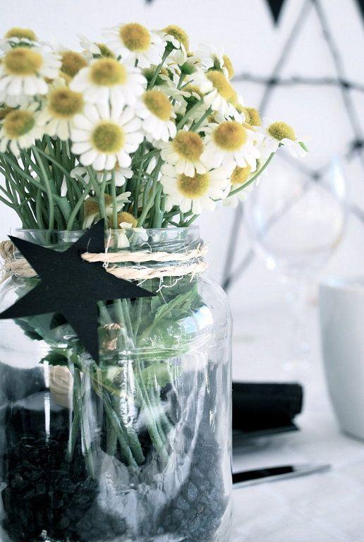 Centros de flores hechos con botes de conservas, estrellas de cartulina y flores artificiales