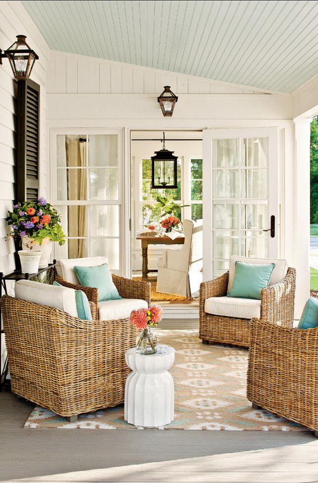 Patio decorating ideas.Rugs define the dining room as a separate area from the connecting kitchen and ground the arrangement of chairs on the porch.  The porch ceiling's pale blue hue is carried through to the pillows and rug. Stools stand in as side tables.  Ceiling Paint Color: Sherwin-Williams SW6210 Window Pane  Rug is the Suzanne Kasler Ikat Rug for Ballard Designs.